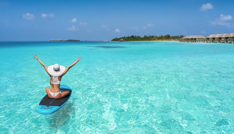 Frau auf Surfbrett auf den Malediven
