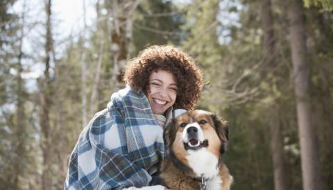 Frau kuschelt mit Hund in Winterlandschaft