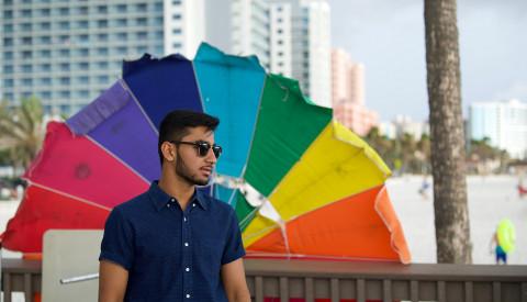 Mann vor Regenbogenschirm