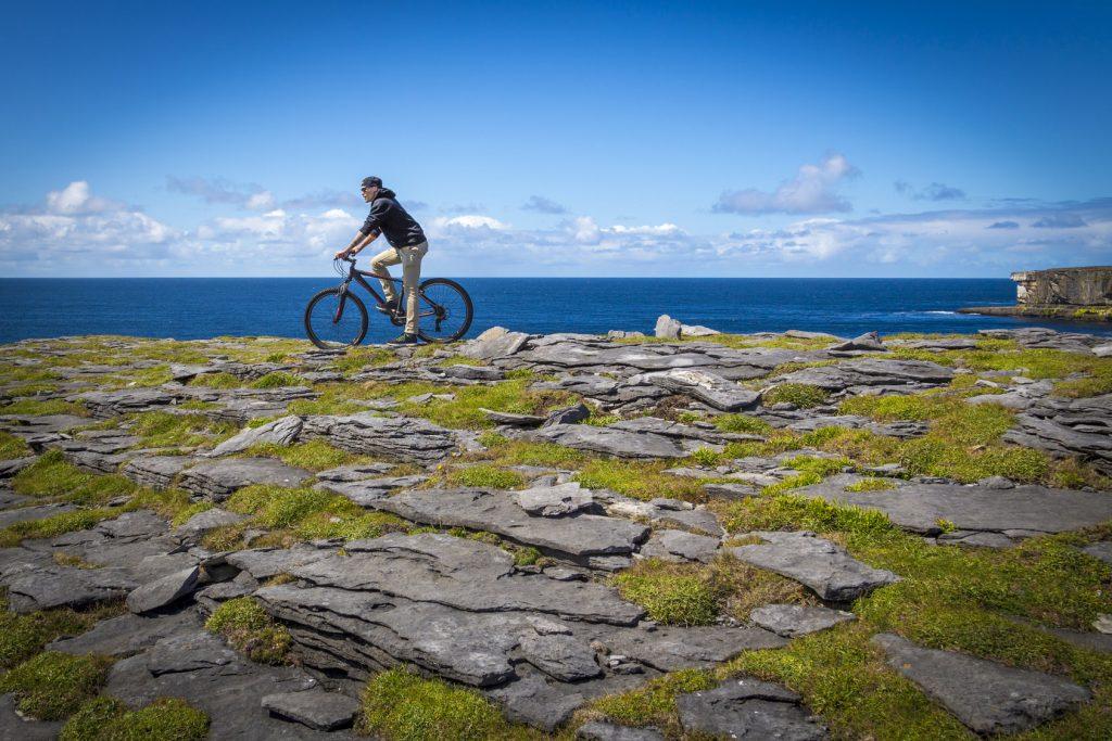 Die schroffe Meeresküste, grüne Wiesen, aber auch verwunschene Wälder und verschlafene Ortschaften lassen sich beim Radeln auf Irland erkunden.