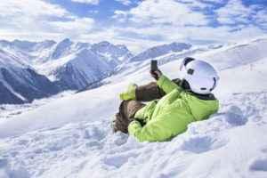 Junger Mann mit Smartphone im Schnee