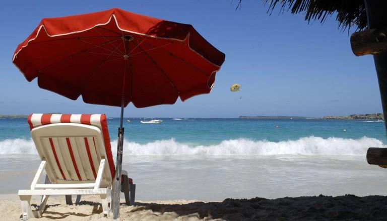 Urlaub am Strand mit Liegestuhl und Sonnenschirm