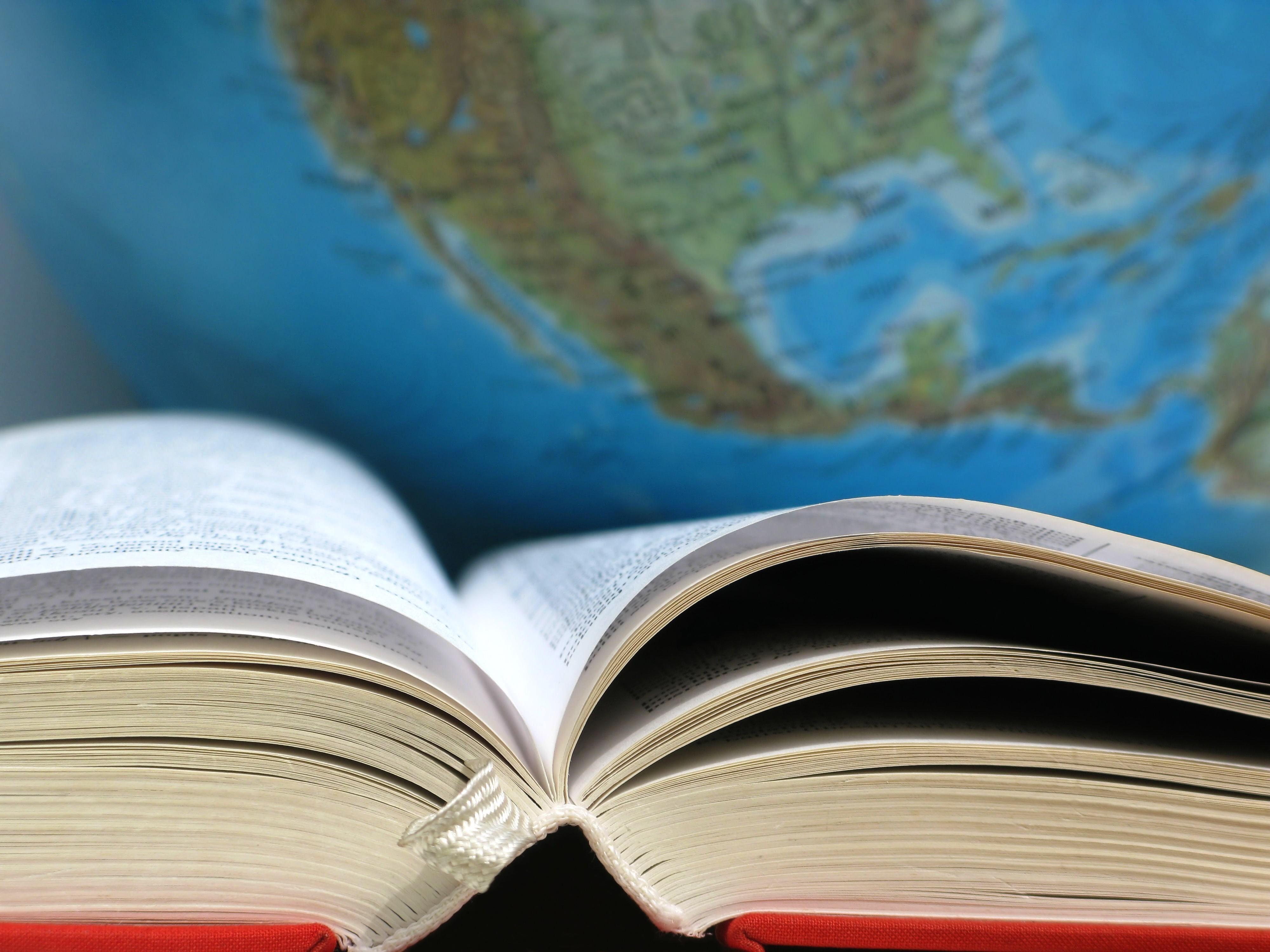 aufgeklapptes Buch mit Weltkugel im Hintergrund