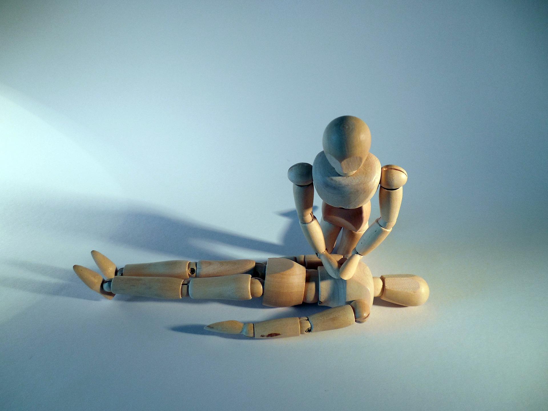 Holz mannequins machen Pose von Herzdruckmassage