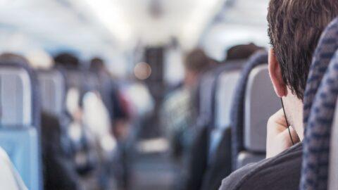 Flugzeugsitzreihe mit Mann auf vorderstem Sitz