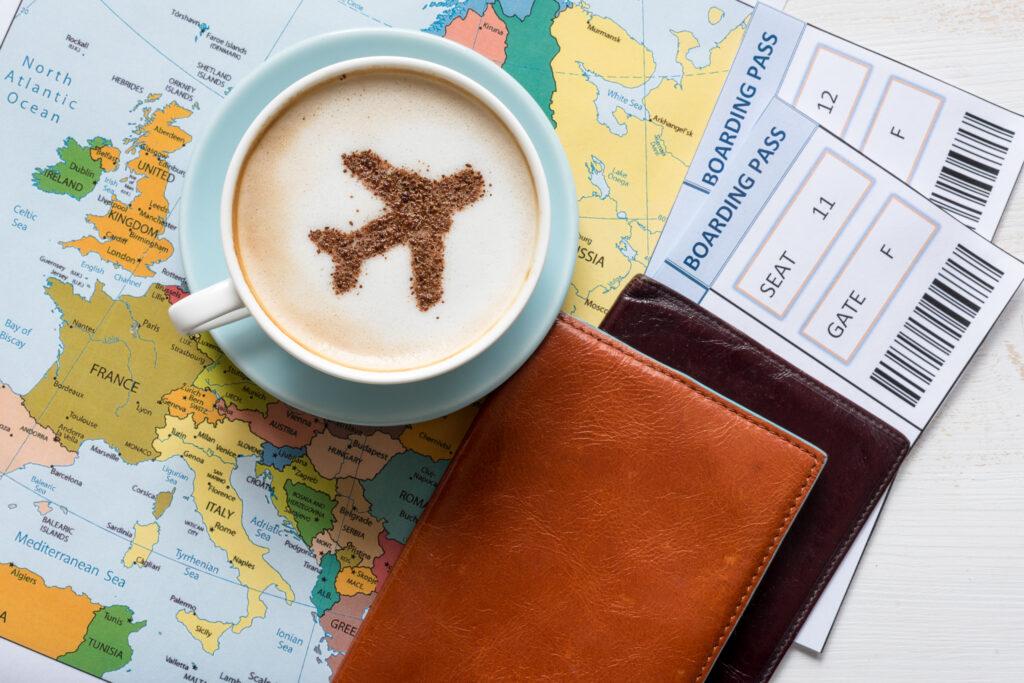 Kaffee in Tasse und Reisepass liegend auf einer Landkarte