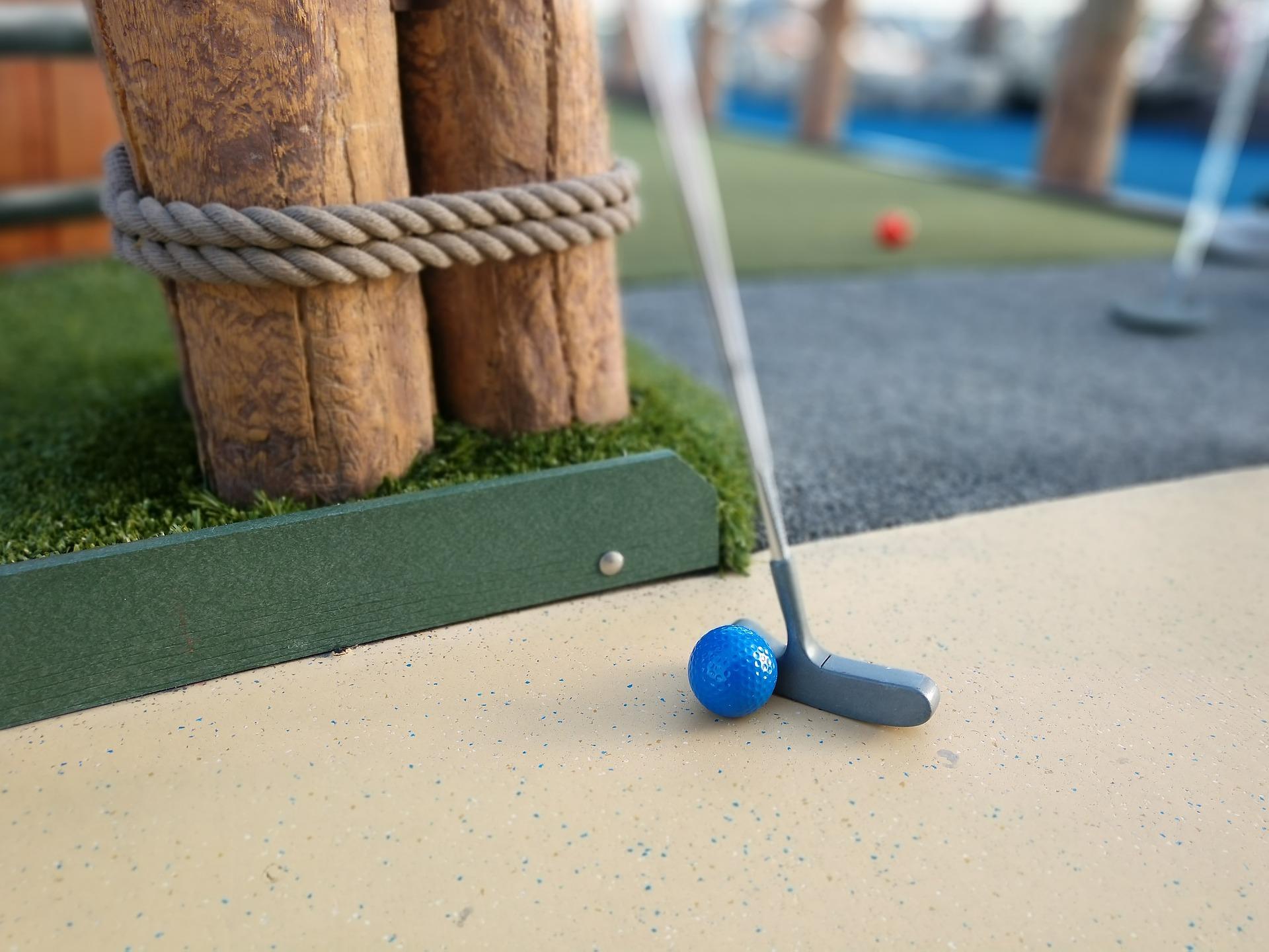 Minigolfschläger und Ball vor einem Zaun