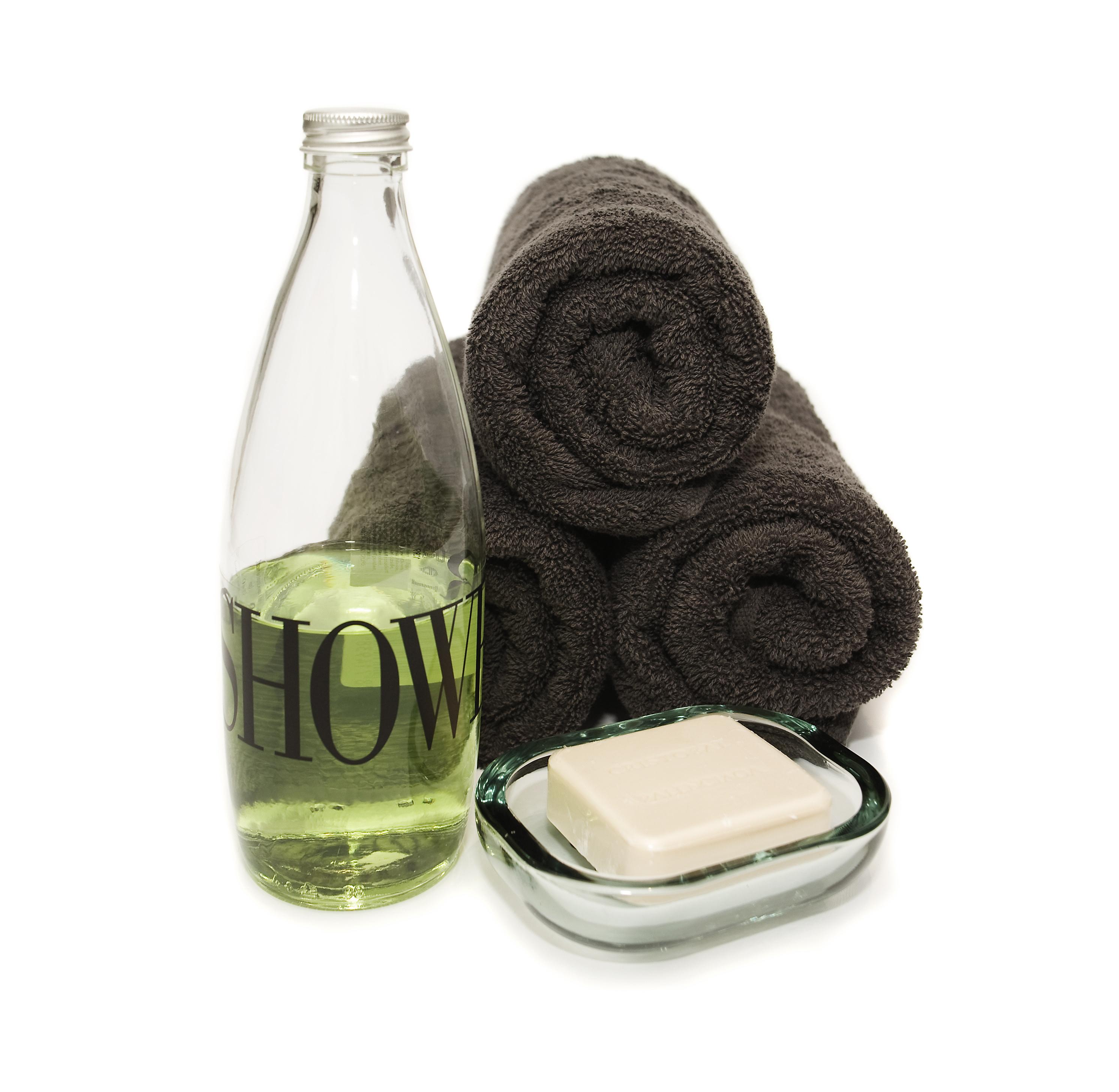 gerollte dunkle Handtücher und eine Seifenschale